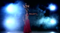 Attractive belly dancer dancing with candles on her head, black, smoke video