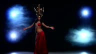 Attractive belly dancer girl starts dancing with candles on her head, black, smoke video