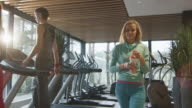 Attractive blond caucasian girl is drinking a protein shake drink while walking next to a treadmill in the sport gym. video