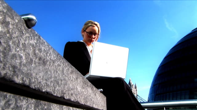 Attractive blond on laptop in the city video