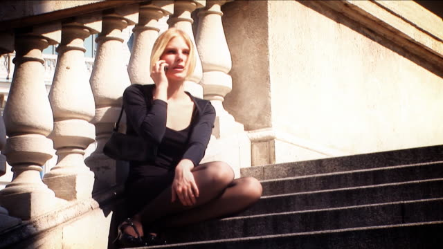 Attractive blond on mobile in black dress video