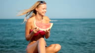 Attractive blond woman eating watermelon on beach video