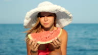 Attractive blond woman in hat eating watermelon on beach video
