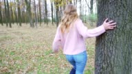 Attractive blonde girl hiding in the forest and leaning against the old tree video