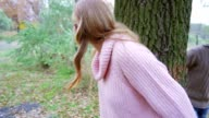 Attractive blonde girl hiding in the forest and leaning against the old tree, playing video