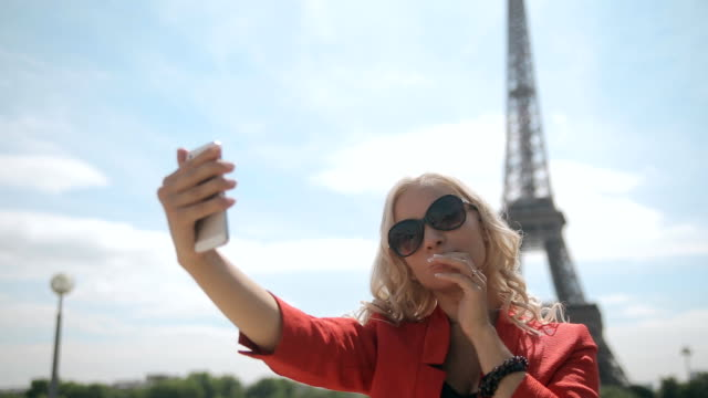 Attractive blonde in sunglasses doing selfie against the backdrop of the Eiffel Tower in Paris video