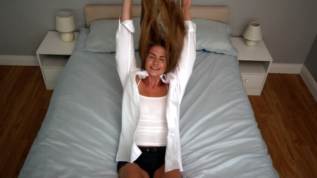 Attractive blonde letting herself falling on bed video