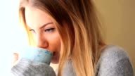 Attractive blonde wearing winter clothes drinking coffee video