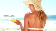 Attractive blonde with hat putting sun cream video