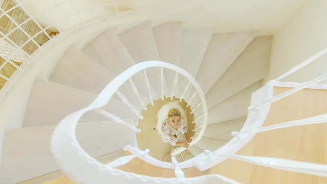 Attractive bride in a beautiful lingerie stands within a spiral staircase. View from above video