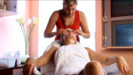 Attractive brunette gets facial treatment from beautiful blond therapist video