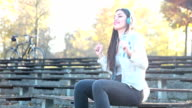 Attractive brunette woman listening to music with headphones at park video