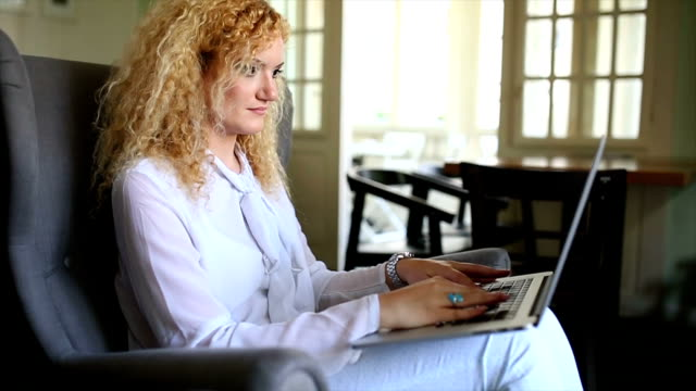 Attractive businesswoman sitting at sofa in living room and typing on lap top video