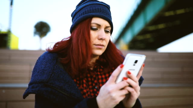 Attractive casual female sits on the steps and using cell phone video