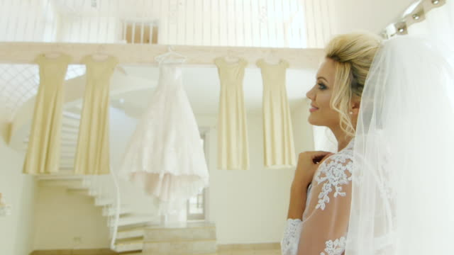 Attractive Caucasian bride looks at her wedding dress and bridesmaids' dresses. Rear view over the shoulder video