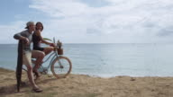 Attractive caucasian couple sitting on bike next to the ocean video
