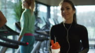 Attractive caucasian girl is drinking a protein shake drink next to a treadmill in the sport gym. video