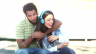 Attractive couple having fun listening to music with headphones video