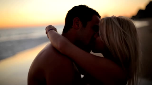 Attractive couple kiss on beach video