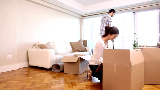 Attractive couple unpacking boxes in their living room video