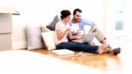 Attractive couple using laptop on the floor video