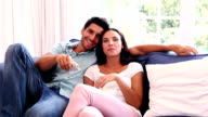 Attractive couple watching tv on the couch video
