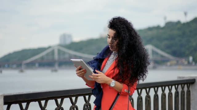 Attractive curly woman with tablet at the bridge background video