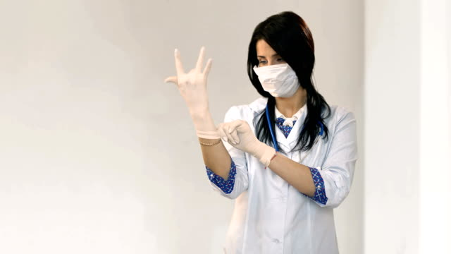 Attractive doctor puts on gloves in white room video