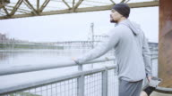 Attractive ethnic male exercising/stretching outdoors video