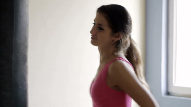 Attractive female kickboxing, black punching bag video