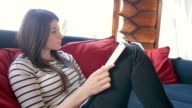 Attractive female reading a book while sitting on a sofa in the mountain cabin. video
