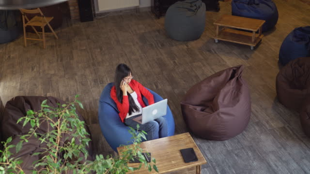 Attractive female works with laptop has business conversation video