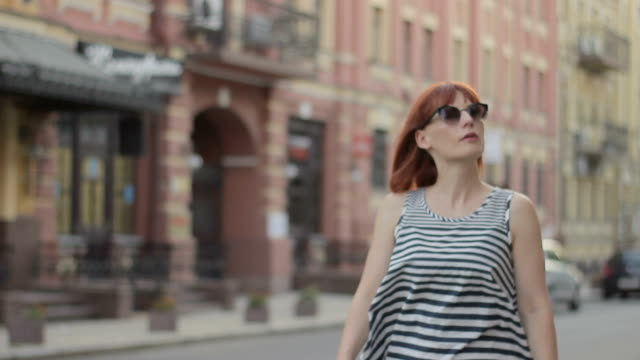 Attractive foreign red-haired woman looking on printed paper map video