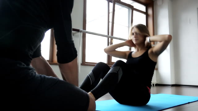 attractive girl athlete work abdominal, and the man in the coach she helps video