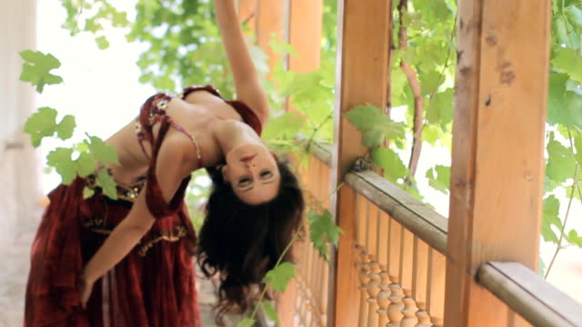 Attractive girl beautifully dancing oriental dance in the gazebo with vine video