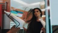 Attractive girl dry hair by hairdryer in bathroom at mirror. Dancing. Posing video