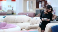 Attractive girl in a black dress, walking on the furniture store holding a tablet in hands. video