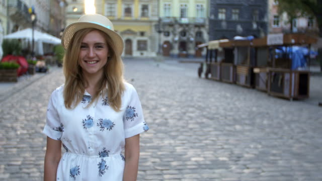 Attractive girl in hat goes down the street in a old city, sun is shining. video