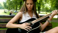 Attractive girl learning how to play guitar in the park video
