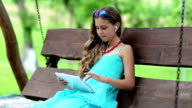 Attractive girl sits on swing bench and holds in hands tablet computer video