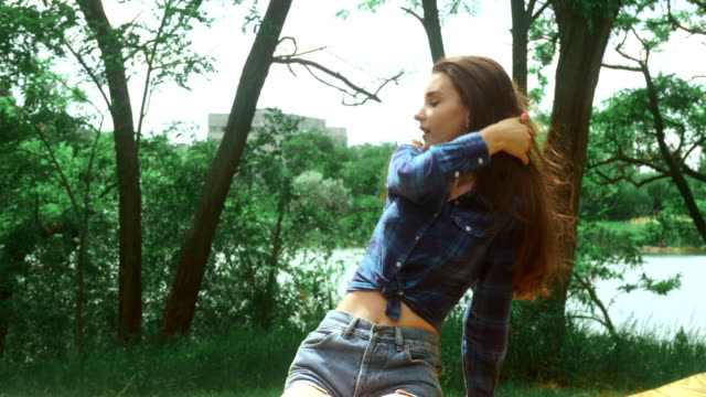 attractive girl sitting on a bench in the Park and the wind stirs her hair video