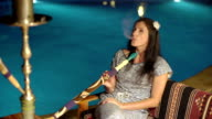 Attractive girl smoking hookah near the pool with blue water background. video