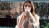 Attractive girl with cup of coffee standing in front of show-window. dreams to buy something, sighs. Slow motion video