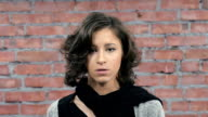Attractive girl with curly hair depict sadness in camera. Casting. Brick wall video