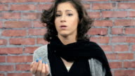 Attractive girl with curly hair sadly panhandle in camera. Casting. Brick wall video