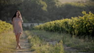 Attractive girl with long black hair walk between the rows of the vineyard video