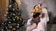 Attractive girl with presents giving gift into camera near Christmas tree video