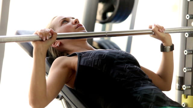 Attractive girl works with Barbell in modern gym video