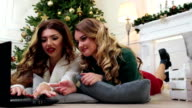 Attractive Girlfriends, using laptop and smiling at camera, Winter weekend near decorated fireplace during New Year Eve, winter holiday, girls print on the keyboard, communicate via the Internet video