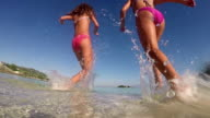 Attractive girls playing in the sea with a splash of water toward camera, SLOW MOTION video